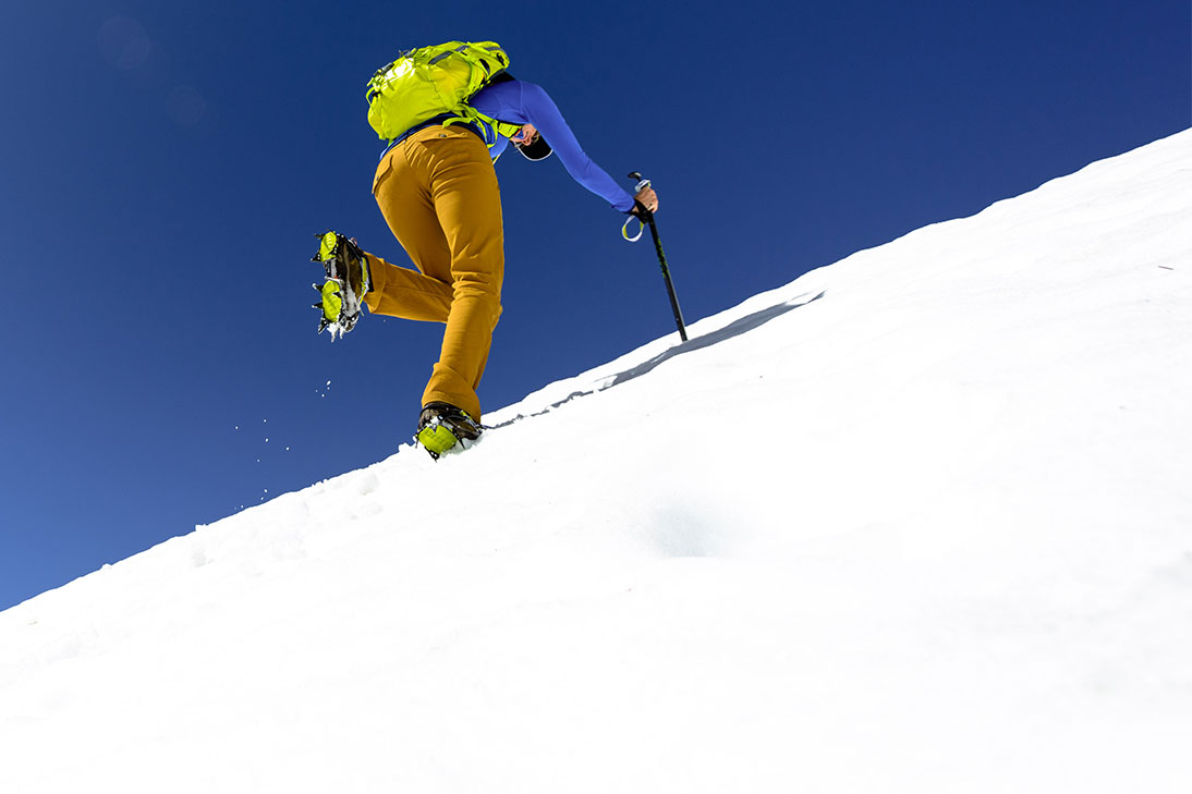 Woman climbing on steep snowy mountain top on sunny day