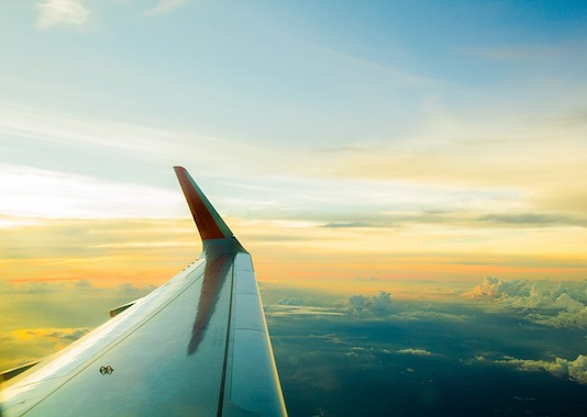 Sunset view over the wing of an airplane while flying